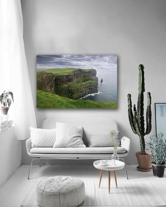 tableau design paysage au dessus d'un canapé blanc